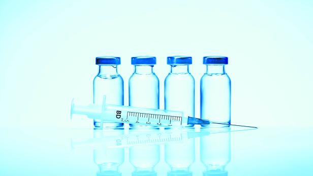 Monochromatic image of four glass vials and a syringe