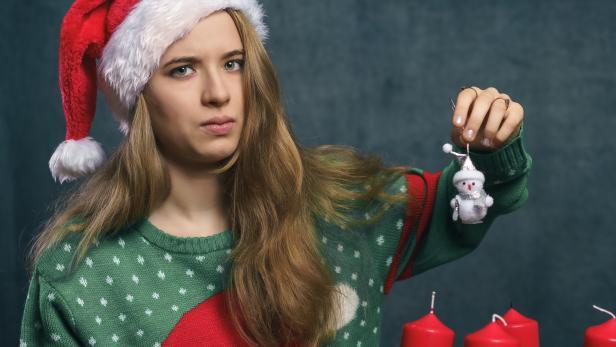 Jugendliche mit Weihnachtsmütze, Schneemann-Figur und Adventkranz