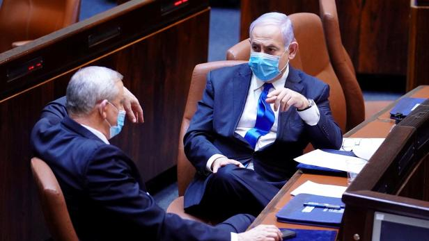 Israeli Prime Minister Benjamin Netanyahu and Benny Gantz, wear face masks as they talk during a swearing in ceremony of the new government, at Israel's parliament, in Jerusalem