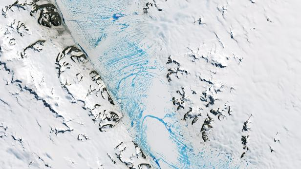 Blue meltwater spans a vast area on the George VI ice shelf in Antarctica