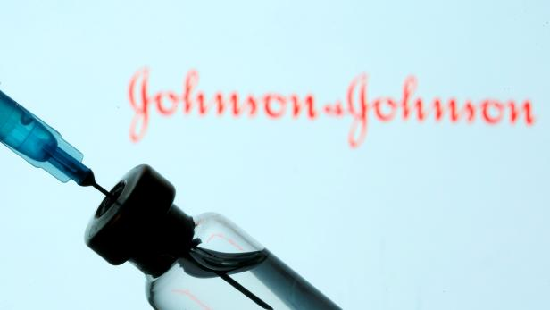 FILE PHOTO: Vial and sryinge are seen in front of displayed Johnson&Johnson logo in this illustration taken