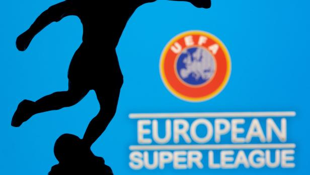 """A metal figure of a football player with a ball is seen in front of the words """"European Super League"""" and the UEFA logo in this illustration"""