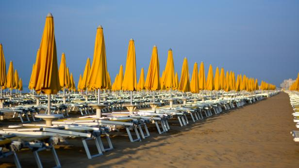the yellow umbrellas still closed and the deckchairs still to be opened