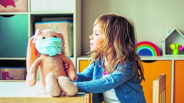 Little girl playing with rabbit soft toy in the medicine mask