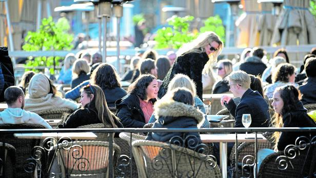 FILE PHOTO: People enjoy the sun at an outdoor restaurant, despite the continuing spread of coronavirus disease (COVID-19), in Stockholm