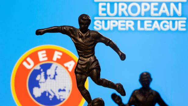 """FILE PHOTO: Metal figures of football players are seen in front of the words """"European Super League"""" and the UEFA logo in this illustration"""