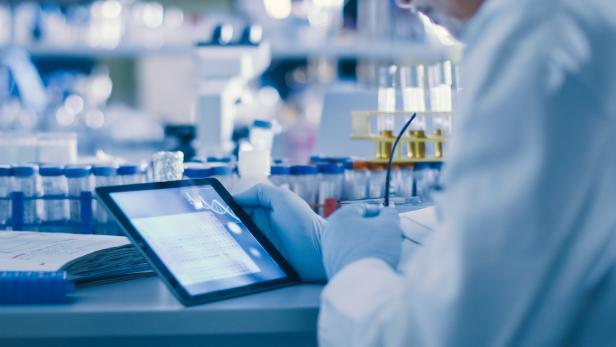 Labor-Arbeiter mit Proberöhrchen und Tablet