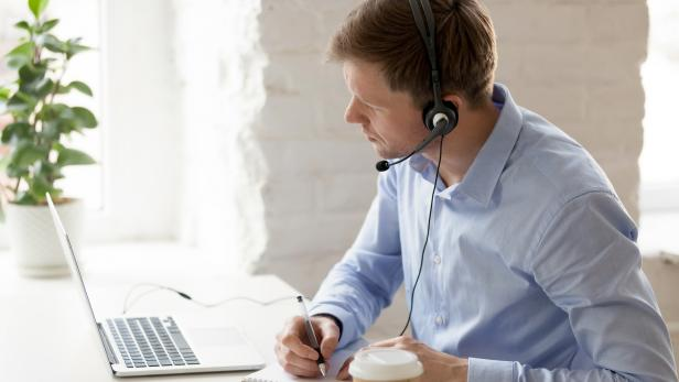 Businessman sitting at workplace improve knowledge using online lessons
