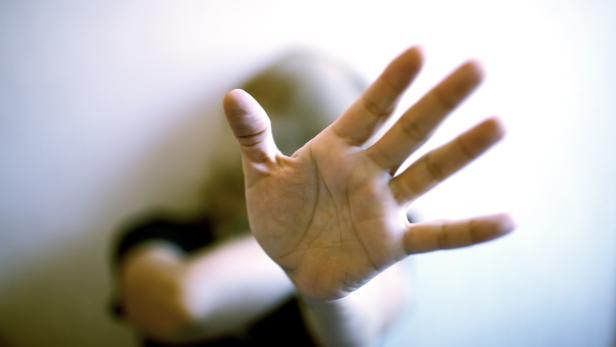 A young woman protects herself by exposing her hand in front of her