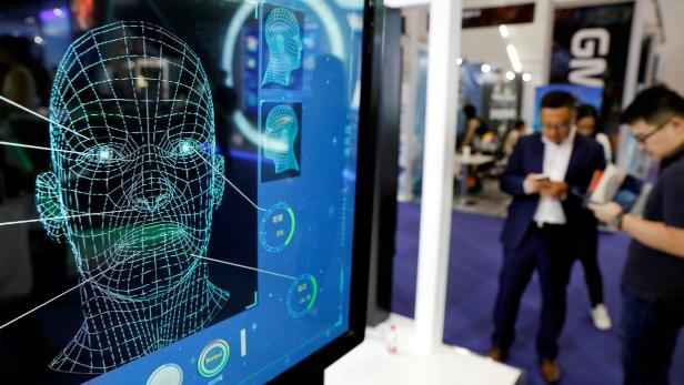 FILE PHOTO: Visitors check their phones behind the screen advertising facial recognition software during Global Mobile Internet Conference (GMIC) at the National Convention in Beijing