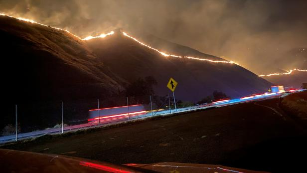 The Shell Fire burns vegetation on a hill along a highway in Kern County, California