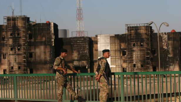 Members of Iraqi police stand guard in front of Maysan Governorate building, which was burnt by demonstrators during a protest over unemployment, corruption and poor public services, in Maysan province, south of Bagdad