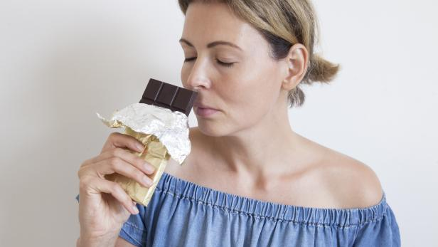 Portrait of a young beautiful girl with blond hair, bare shoulders and a neck, holding a chocolate bar to enjoy the taste. Sweet eating and organic products, a sense of temptation