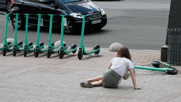 A woman lies on the ground after falling off an e-scooter in central Kyiv