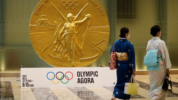 Women walk past a large-scale reproduction of Tokyo 2020 Olympic Games medal at Nihonbashi Mitsui Tower in Tokyo