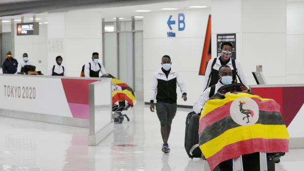 Members of Uganda's Olympic team leave at Narita international airport after a member of the team has tested positive for the coronavirus disease (COVID-19) and was barred entry into Japan, in Narita, east of Tokyo