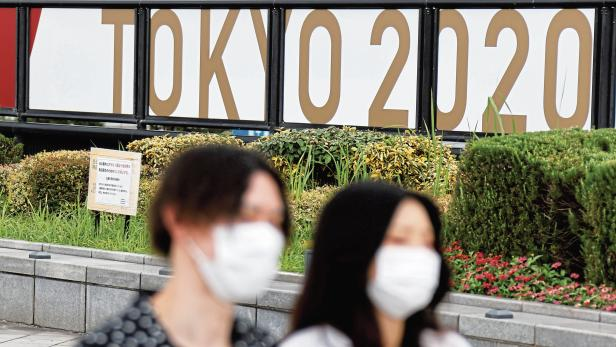 People wearing protective masks walk past banners advertising the 2020  Olympic Games in Tokyo