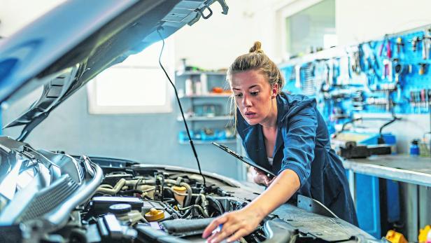 Lovely female auto mechanic, examining engine of an automobile
