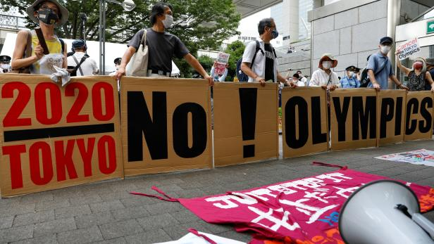 Anti-olympic protesters outside Tokyo Metropolitan Government building during the arrival ceremony for the Olympic flame of the Tokyo 2020 Olympic Torch Relay, on the day of the start of the Tokyo 2020 Olympics in Tokyo