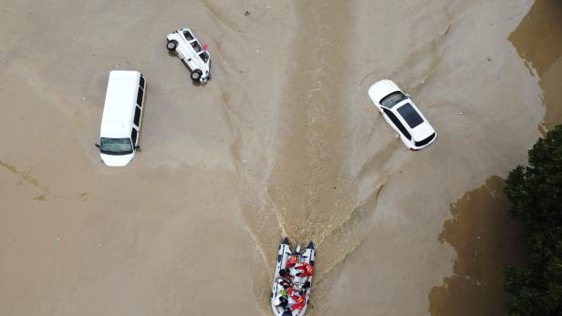 Rescue workers evacuate residents on a boat past stranded vehicles following heavy rainfall in Zhengzhou