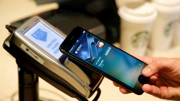 FILE PHOTO: Man uses iPhone 7 smartphone to demonstrate mobile payment service Apple Pay at cafe in Moscow