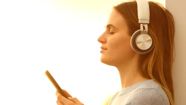Girl listening to music with headphones and phone