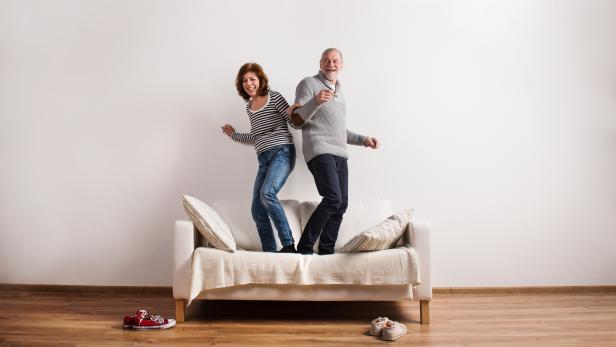 Beautiful senior couple standing on couch, dancing. Studio shot.