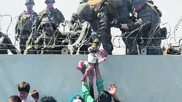 FILE PHOTO: A baby is handed over to the American army over the perimeter wall of the airport in Kabul