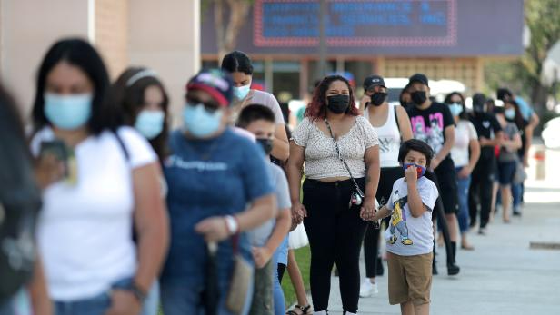 FILE PHOTO: People wait in line for a COVID-19 test at a back-to-school clinic in Los Angeles