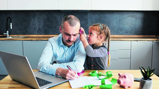 Father Working from home on laptop during quarantine. Young father does homework with his little daughter