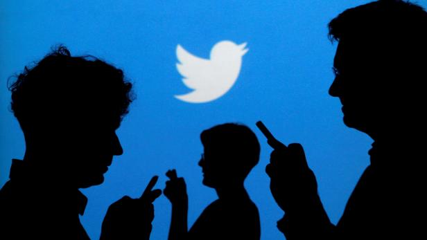 FILE PHOTO: FILE PHOTO: People holding mobile phones are silhouetted against a backdrop projected with the Twitter logo  in Warsaw