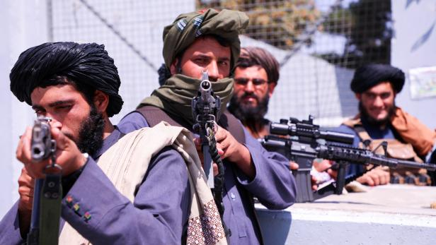 Taliban forces stand guard in front of Hamid Karzai International Airport in Kabul