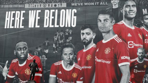 A picture of Cristiano Ronaldo with teammates is displayed on the outside of Old Trafford