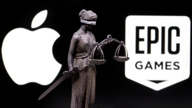 FILE PHOTO: 3D printed Lady Justice figure is seen in front of displayed Apple and Epic Games logos in this illustration photo