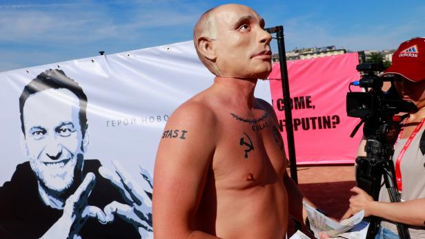 A protester wearing a mask of Russian President Vladimir Putin throws fake bank notes in front of a poster of Alexei Navalny ahead of a meeting between U.S. President Biden and Russian President Putin in Geneva