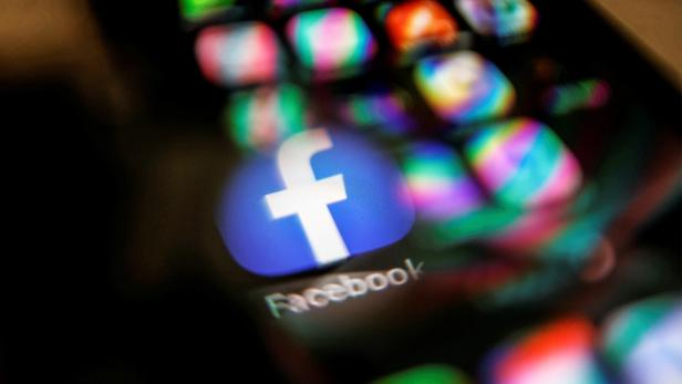 FILE PHOTO: Facebook logo displayed on a mobile phone is seen through a magnifying glass in this picture illustration