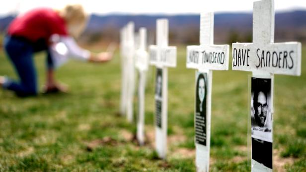 A woman looks at a line of crosses commemorating those killed in the Columbine High School shooting on the 20th anniversary of the attack in Littleton