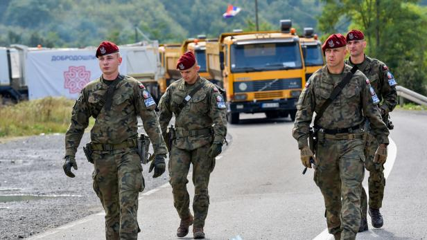 FILE PHOTO: Polish soldiers, part of the peacekeeping mission in Kosovo, KFOR, pass through barricades near the border crossing between Kosovo and Serbia in Jarinje, Kosovo, September 28,