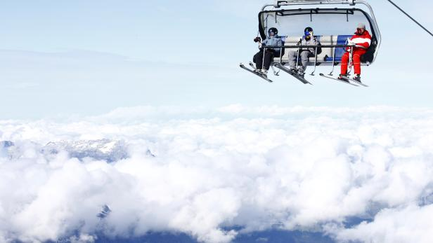 Skiers sit in a chair lift at Mount Titlis skiing area near Engelberg
