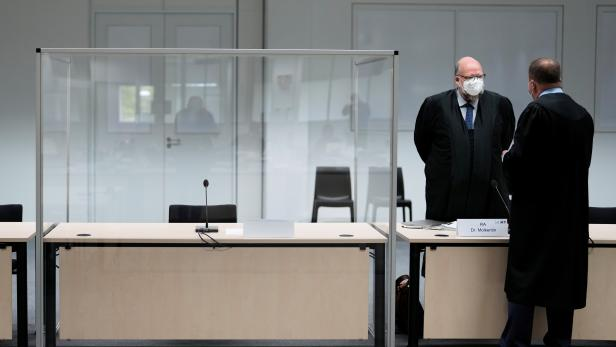 Two lawmakers stand next to the empty seat of the accused 96-year-old former secretary to the SS commander of the Stutthof concentration camp before a trial against her, in Itzehoe