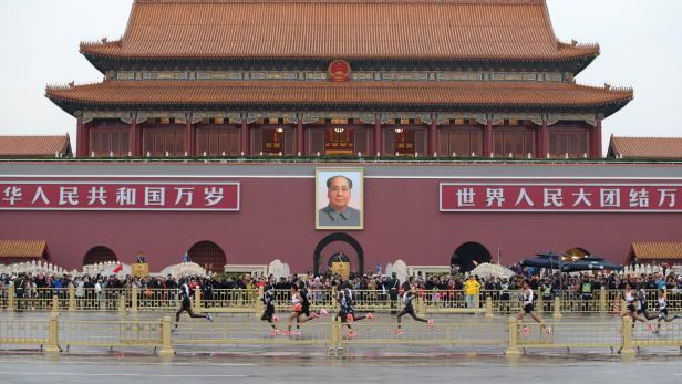 Leading athletes run past Tiananmen Gate during the annual Beijing Marathon in Beijing
