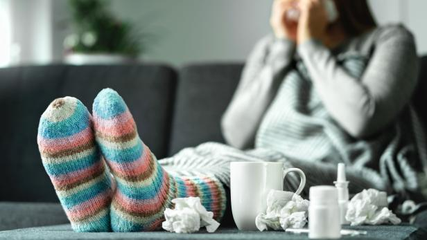 Sick woman with flu, cold, fever and cough sitting on couch at home. Ill person blowing nose and sneezing with tissue and handkerchief. Woolen socks and medicine. Infection in winter.