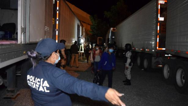 A police officer gives instructions to migrants, in Ciudad Victoria