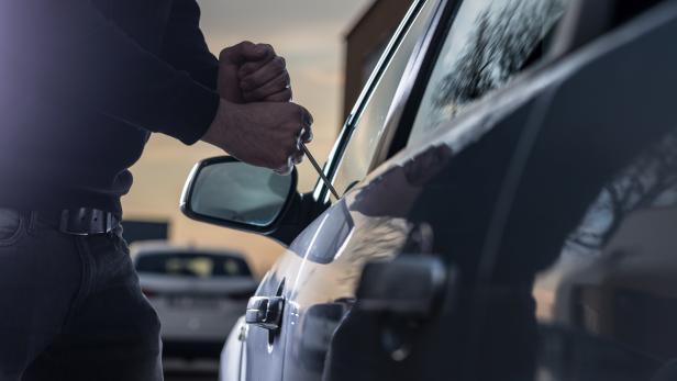 Auto thief in black balaclava trying to break into car